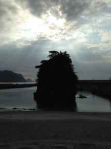 朝日を浴びる海岸に突き出た岩